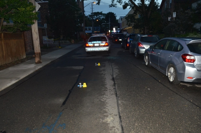 A northbound view of WO #2 and WO #3's police cruiser on Bowden Street. Two nickel cartridge cases, indicated by yellow evidence markers, were located just south of the cruiser.