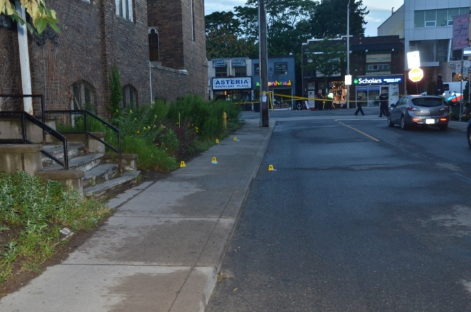 The west sidewalk of Bowden Street across the street from 7Numbers restaurant. Yellow evidence markers indicate the locations of the five brass cartridge cases that were found.
