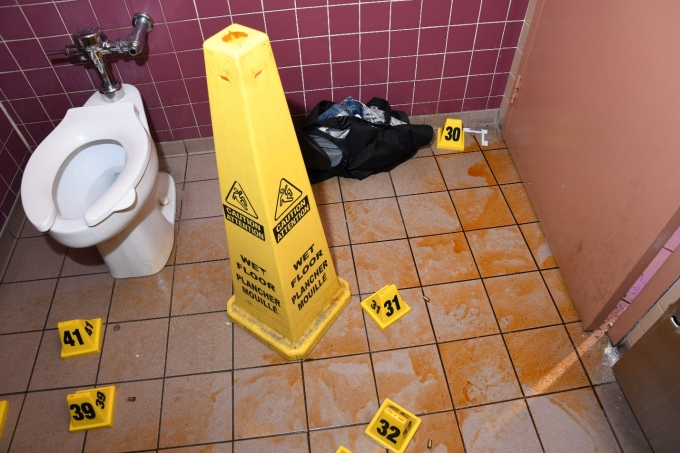 Figure 3 – the interior of the washroom with oily residue (likely from the OC spray) and cartridge cases/bullet fragments marked with yellow evidence markers.