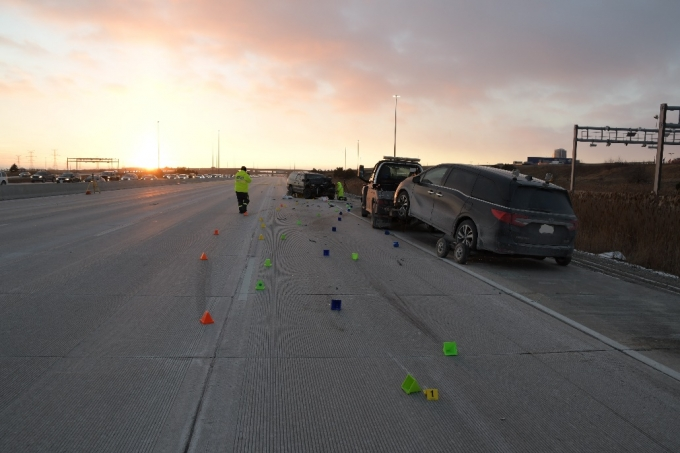 "The undamaged tow truck and vehicle that were also on the scene. The yellow evidence marker ""1"" in the foreground indicates the first gouge in the concrete and is the best indication of the area of impact for the collision."