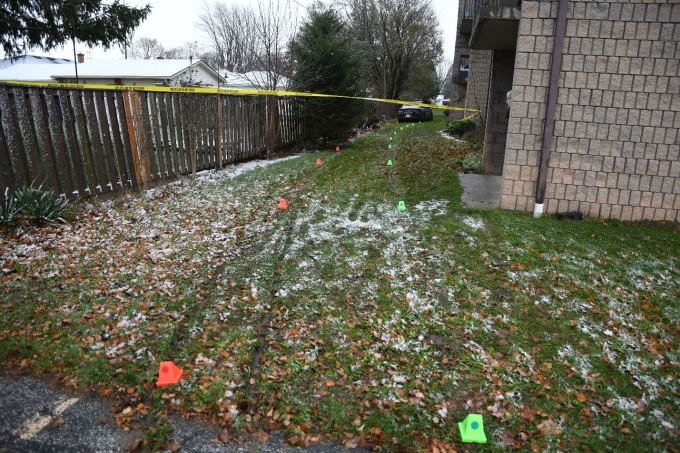 The grassy yard running behind 53 McNaughton Avenue West where the collision occured. Green and orange evidence markers mark the tire tracks of the CKPS cruiser (visible in the distance) which struck the Complainant.