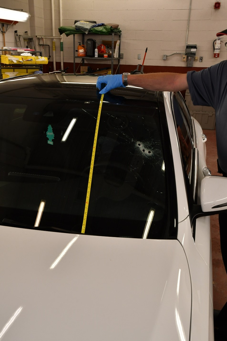 Figure 1- The front windshield of the Mercedes Benz C300 with three bullet holes on the driver's side.
